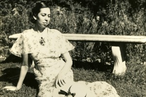 Eudora seated in front of garden bench, 1930s.