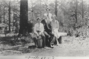 Walter, Christian, Edward, and Chestina sitting on garden bench in front side yard, 1920s.